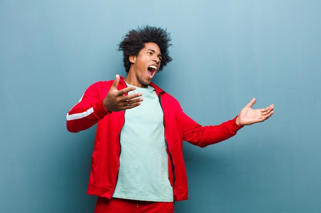 젊은 흑인 스포츠 남자 오페라를 수행하거나 콘서트 나 쇼에서 노래, 로맨틱하고 예술적이며 그런지 벽에 대한 열정 프리미엄 사진