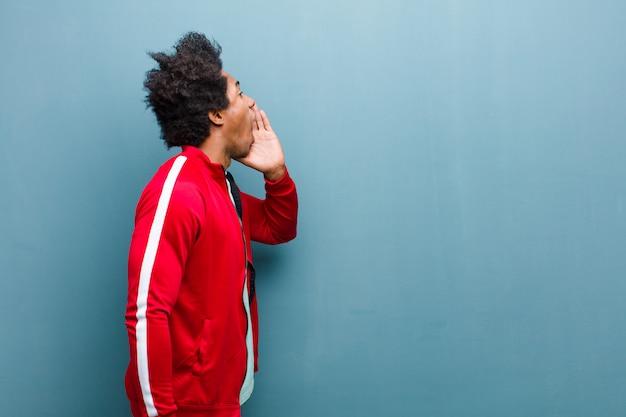 若い黒のスポーツ男プロフィールビュー、幸せそうに見えて興奮して、叫んで、グランジの壁に対して側にスペースをコピーするように呼び出す