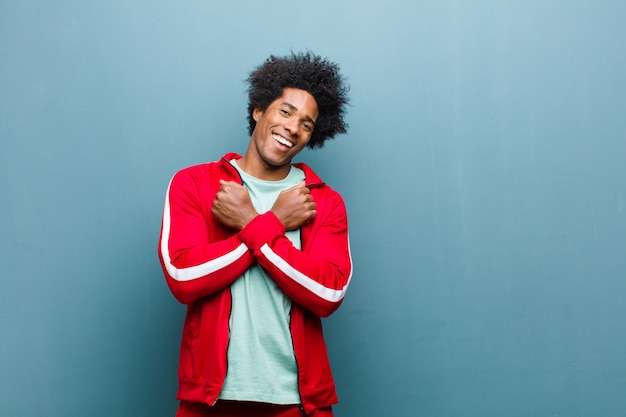Young black sports man smiling cheerfully and celebrating, with fists clenched and arms crossed, feeling happy and positive against grunge wall