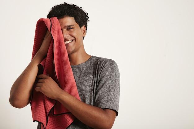 Il giovane sportivo nero ride e si asciuga il viso con un asciugamano rosso, metà destra del viso aperta su bianco