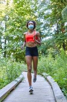 Молодая черная спортсменка девушка бегает в парке