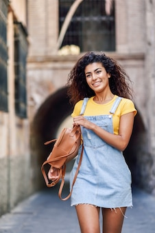 Young black tourist woman with curly hairstyle outdoors