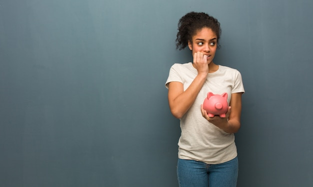 Young black woman biting nails, nervous and very anxious. she is holding a piggy bank.