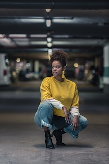 Young black woman in bright trendy outfit squatting on parking lot