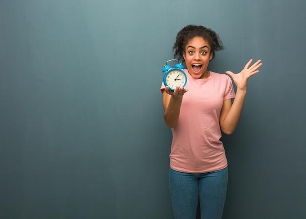 勝利または成功を祝っている若い黒人女性。彼女は目覚まし時計を持っています。