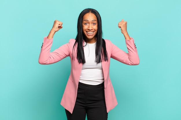 Молодая чернокожая женщина празднует невероятный успех как победитель, выглядит взволнованной и счастливой, говоря: «возьми это!». бизнес-концепция