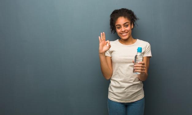 若い黒人女性は陽気で自信を持ってokのしぐさをしています。彼女は水のボトルを持っています。