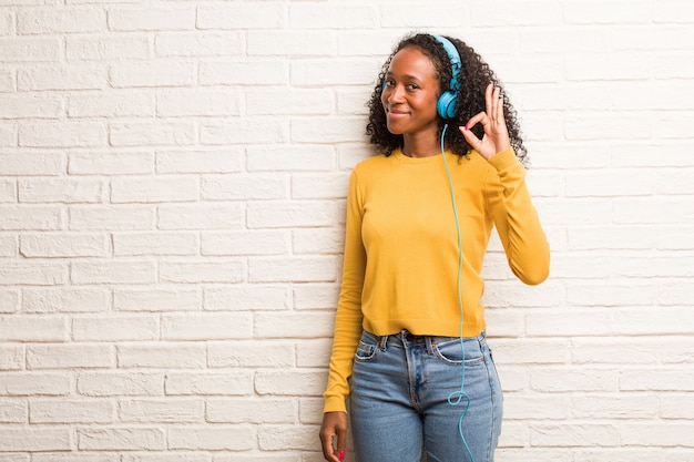 Young black woman cheerful and confident doing ok gesture, excited and screaming