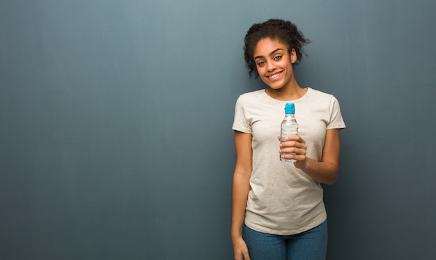 水のボトルを保持している大きな笑顔で陽気な若い黒人女性。