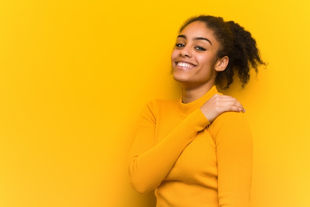 Young black woman closeup over an orange wall