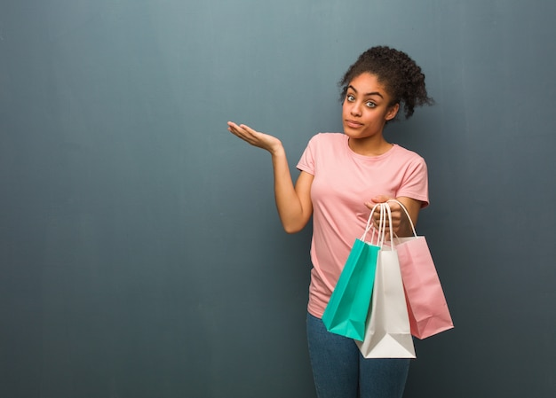 Young black woman confused and doubtful. she is holding a shopping bags.