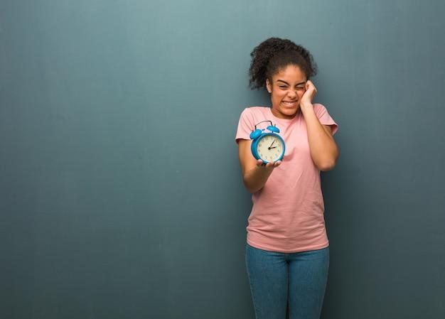 若い黒人女性の手で耳を覆っています。彼女は目覚まし時計を持っています。