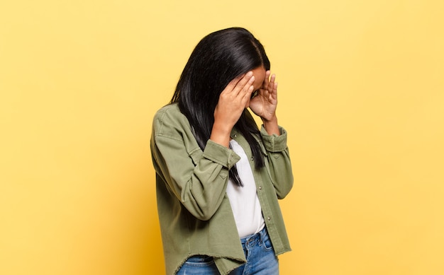 절망의 슬프고 좌절한 표정으로 손으로 눈을 덮고 있는 젊은 흑인 여성, 울고, 옆모습