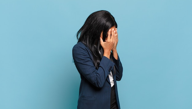 Young black woman covering eyes with hands with a sad, frustrated look of despair, crying, side view. business concept
