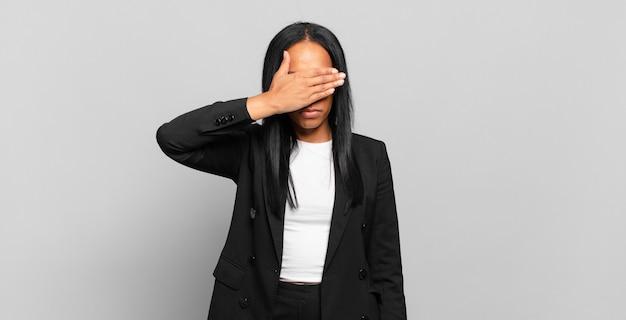 片手で目を覆っている若い黒人女性は、恐怖や不安を感じ、不思議に思ったり、盲目的に驚きを待っています。ビジネスコンセプト