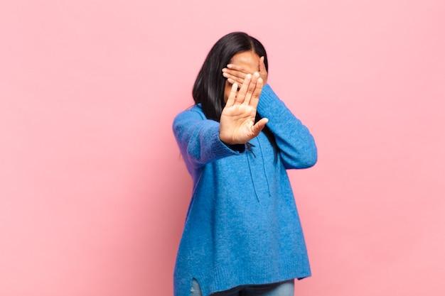 젊은 흑인 여성이 손으로 얼굴을 덮고 다른 손을 앞에 올려 카메라를 멈추고 사진이나 그림을 거부합니다.