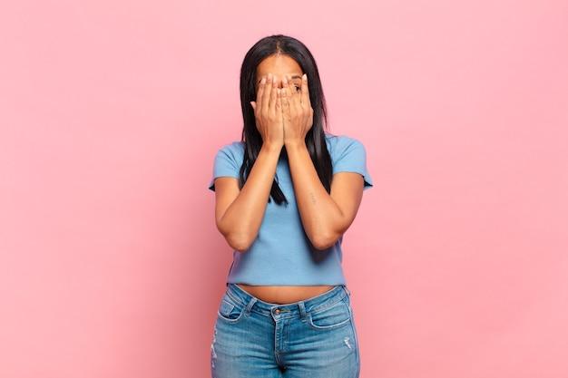Молодая темнокожая женщина закрыла лицо руками, с удивлением выглянула между пальцев и посмотрела в сторону