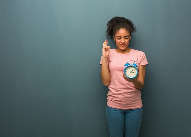 Young black woman crossing fingers for having luck. she is holding an alarm clock.