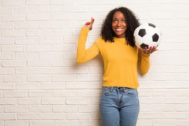 Молодая негритянка скрещивает пальцы, хочет быть удачливой для будущих проектов, взволнованная, но взволнованная, нервное выражение, закрывающее глаза
