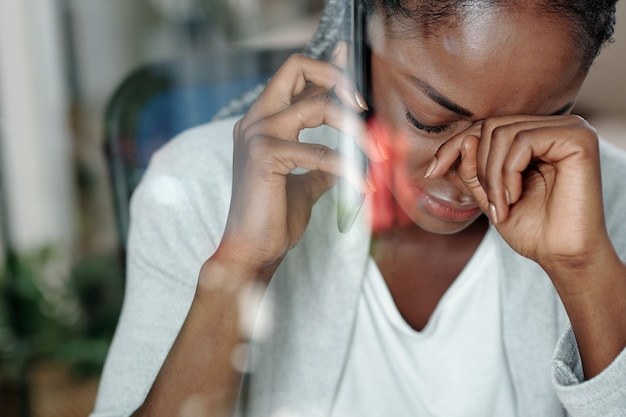 전화로 나쁜 소식을 듣고 우는 젊은 흑인 여성