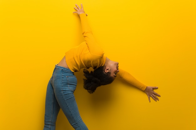Young black woman dancing over an orange wall
