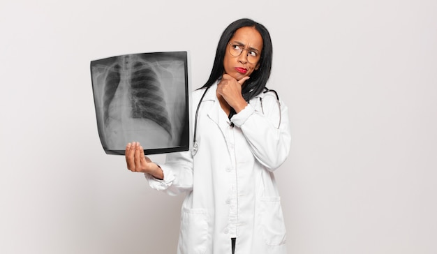 Молодая черная женщина-врач думает, сомневается и смущается