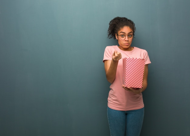 Young black woman doing a gesture of need. she is holding a popcorns bucket.