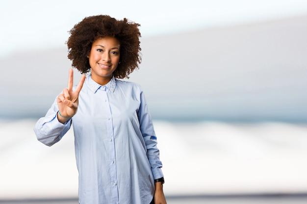 勝利のジェスチャーをしている若い黒人の女性