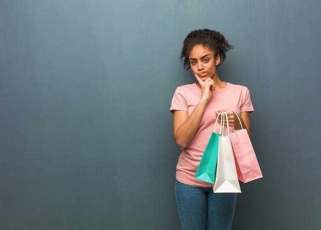 Young black woman doubting and confused. she is holding a shopping bags.
