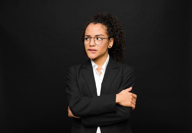 Молодая чернокожая женщина сомневается или думает, кусает губу и чувствует себя неуверенно и нервно, пытаясь скопировать пространство сбоку у черной стены