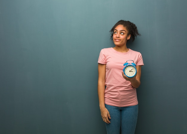 Young black woman dreaming of achieving goals and purposes. she is holding an alarm clock.