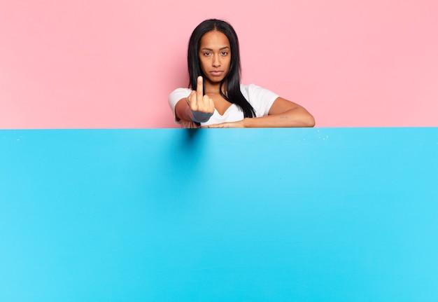 젊은 흑인 여성은 화가 나고 짜증이 나고 반항적이고 공격적이며 가운데 손가락을 뒤집고 반격합니다. 복사 공간 개념