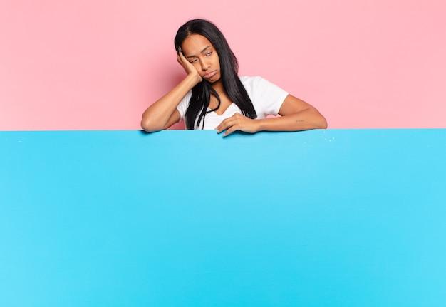 若い黒人女性は、手で顔を持って、退屈で、退屈で、退屈な仕事をした後、退屈で、欲求不満で、眠く感じました。コピースペースの概念