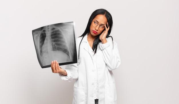 若い黒人女性は、手で顔を持って、退屈で、退屈で、退屈な仕事をした後、退屈で、欲求不満で、眠く感じました。医師の概念