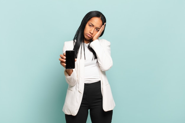 Young black woman feeling bored, frustrated and sleepy after a tiresome, dull and tedious task, holding face with hand. smart phone concept
