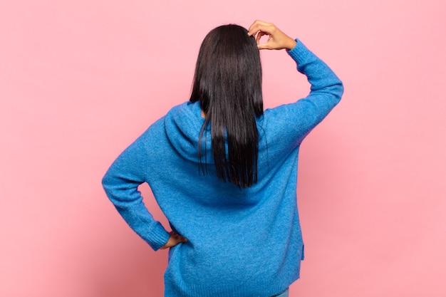 Молодая черная женщина чувствует себя невежественной и сбитой с толку, думая о решении, с рукой на бедре и другой на голове, вид сзади