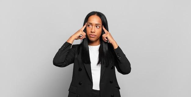 Молодая чернокожая женщина чувствует замешательство или сомневается, концентрируется на идее, напряженно думает, пытается скопировать пространство сбоку. бизнес-концепция