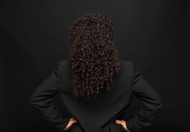 젊은 흑인 여성 혼란 또는 전체 또는 의심과 질문 느낌, 엉덩이에 손으로 궁금, 검은 벽에 후면보기