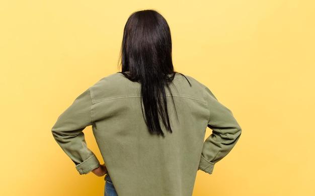 젊은 흑인 여성은 혼란스럽거나 가득 차거나 의심과 질문을 하고, 엉덩이에 손을 얹고, 후면을 봅니다.