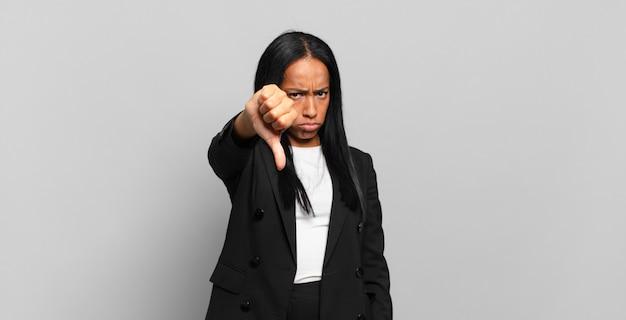 Молодая чернокожая женщина чувствует раздражение, злость, раздражение, разочарование или недовольство, показывая большой палец вниз серьезным взглядом. бизнес-концепция