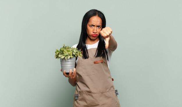 若い黒人女性は、真剣な表情で親指を下に向けて、十字架、怒り、イライラ、失望、または不満を感じています。庭師の概念