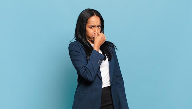 若い黒人女性は嫌悪感を感じ、悪臭や不快な悪臭を避けるために鼻を押さえています。ビジネスコンセプト