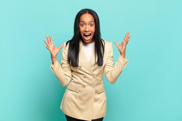 Молодая чернокожая женщина чувствует себя счастливой, удивленной, удачливой и удивленной, и хочет серьезно сказать: «боже»? невероятный. бизнес-концепция