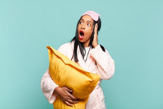 Молодая черная женщина чувствует себя счастливой, взволнованной и удивленной, глядя в сторону обеими руками на лице. концепция пижамы