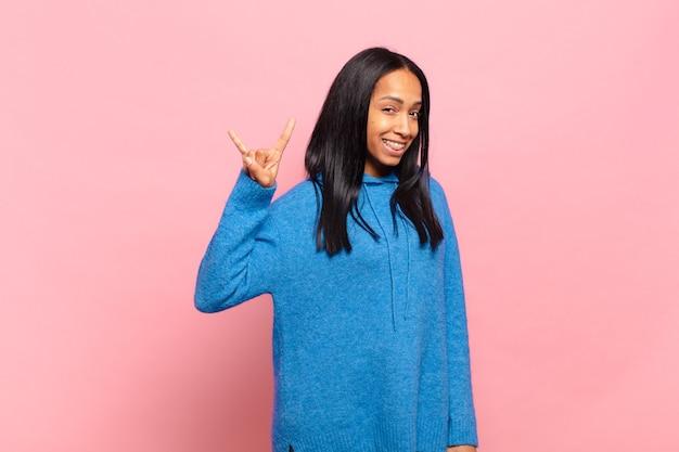 Молодая темнокожая женщина чувствует себя счастливой, веселой, уверенной, позитивной и мятежной, делая знак рок или хэви-метал рукой