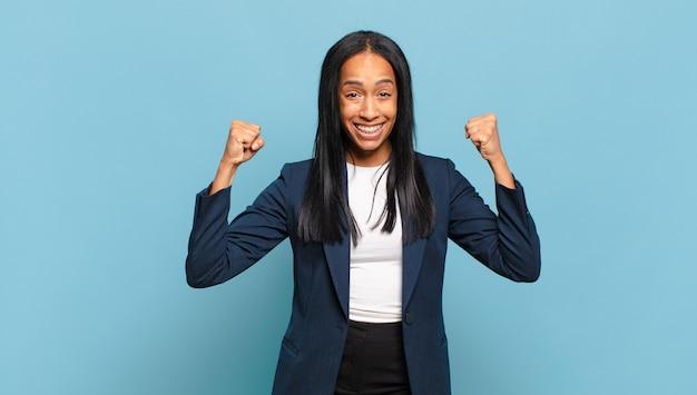 勝利、成果、または幸運を祝って、幸せ、前向き、成功を感じている若い黒人女性。ビジネスコンセプト