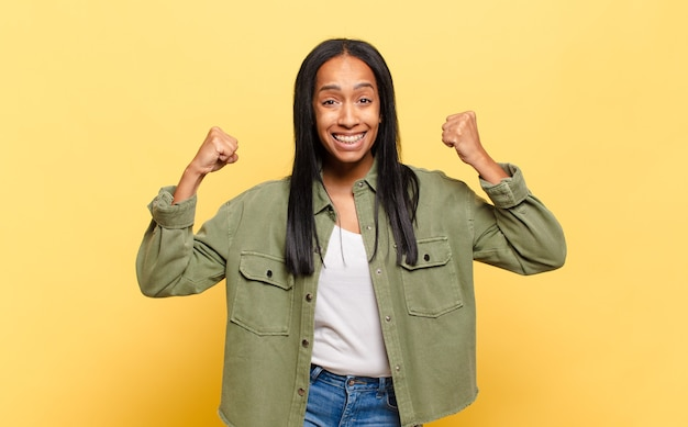 Молодая темнокожая женщина чувствует себя счастливой, позитивной и успешной, празднует победу, достижения или удачу