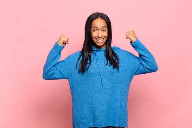 젊은 흑인 여성은 행복하고 긍정적이며 성공하며 승리, 업적 또는 행운을 축하합니다