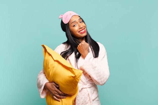 Молодая чернокожая женщина чувствует себя счастливой, позитивной и успешной, мотивированной, когда сталкивается с проблемой или празднует хорошие результаты. концепция пижамы