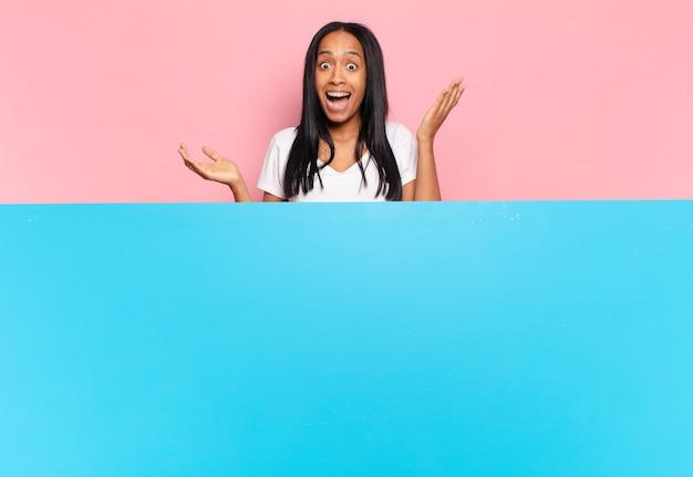 幸せ、驚き、陽気を感じ、前向きな姿勢で笑顔で、解決策やアイデアを実現する若い黒人女性。コピースペースの概念